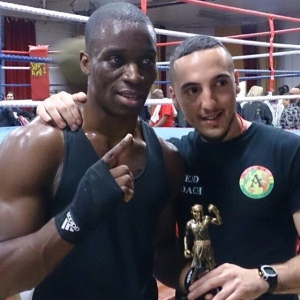 Nyesco with his winners trophy and coach after his bout.
